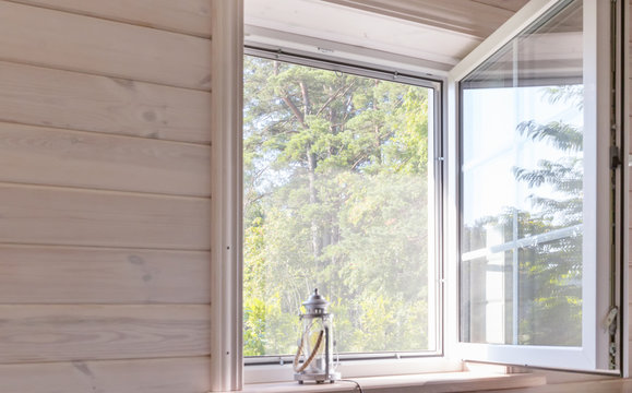White window with mosquito net in a rustic wooden house overlooking the garden, Shallow depth of field