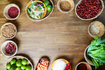 Top view background image of various spices and food ingredients set on wooden table with copy space in center