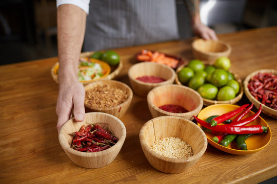 Background image of unrecognizable chef setting ingredients on wooden table while cooking spicy food in restaurant kitchen, copy space