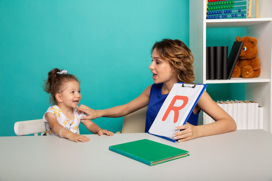 Speech therapy concept. Kid with therapist learning letters together