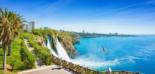 Aerial panoramic image of Lower Duden waterfall in Antalya, Turkey. Water falls drop off rocky cliff directly into Mediterranean sea in sunny summer day.