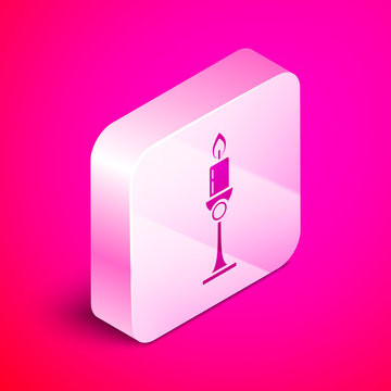 Isometric Burning candle in candlestick icon isolated on pink background. Old fashioned lit candle. Cylindrical candle stick with burning flame. Silver square button. Vector Illustration