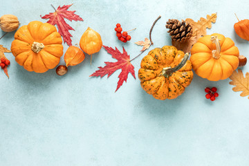Festive autumn pumpkins decor with fall leaves, berries, nuts on blue  background. Thanksgiving day or halloween holiday, harvest concept. Top view flat lay composition with copy space for greeting