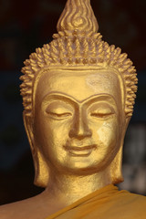 Close up of the face of a golden Buddha sculpture adorned in an orange robe against a black background