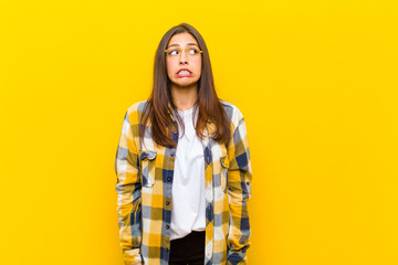 young  pretty woman looking worried, stressed, anxious and scared, panicking and clenching teeth against orange wall Wall mural