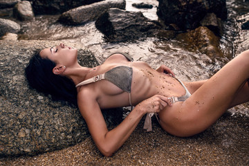A sexy photo of a brunette with long hair posing lying on the yellow sand with her eyes closed in a silver bikini with large breasts among the rocks and the sea coast.