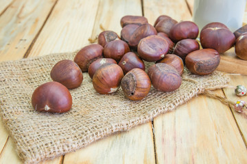 Delicious roasted chestnuts on wood background