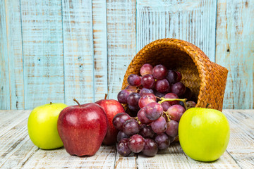 fresh apples with red grapes on wood background