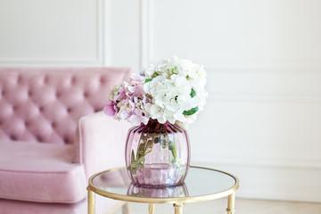 Fond de hotte en verre imprimé Hortensia Bouquet of pastel hydrangeas in glass vase. Flowers in a vase at home. beautiful bouquet of hydrangeas is in a vase on a table near a pink sofa in a white living room. Home interior decor. Scandinavia