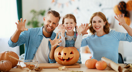 happy  family mother father and child daughter prepare for Halloween decorate  home with pumpkins,  laughing and  play  .