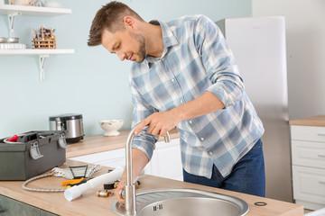 Plumber installing sink in kitchen