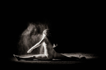 The girl with the flour on the body stretches the arms up with thrown flour on black background black and white image