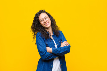 young pretty woman laughing happily with arms crossed, with a relaxed, positive and satisfied pose against orange wall