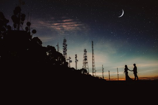 Man and a woman in silhouette holding hands under the starry night sky