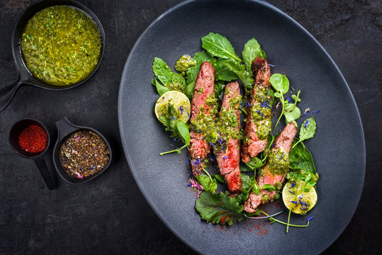 Barbecue wagyu hanging tender steak with chili, lettuce and chimichurri sauce as top view on a modern design plate