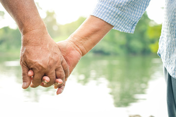 Asian elderly couple holding hands together, love each other and take care of each other forever. The backdrop is a beautiful natural river.