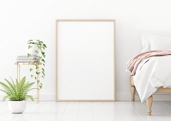 Poster mockup with vertical wooden frame standing on floor in bedroom interior with unmade bed, pink plaid and green plants on empty white wall background. 3D rendering, illustration.