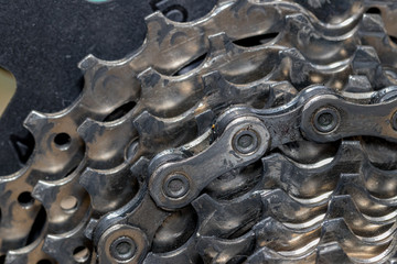 Closeup of dirty bicycle cassette gears and chain links covered in oil, dirt, and debris. Concept of cycling maintenance and repair