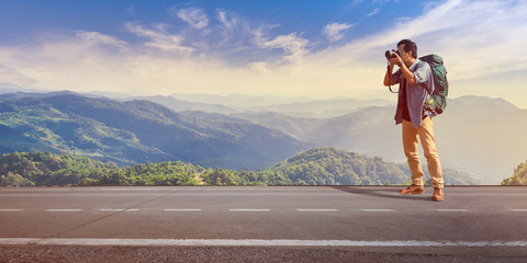 Photographer traveler standing on road who take picture with mountain at sunrise under blue sky