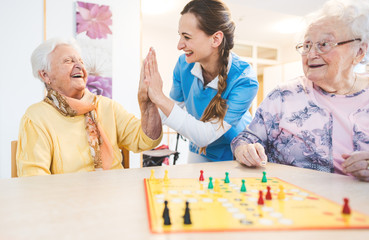Seniors and nurses giving high-five in nursing home playing games