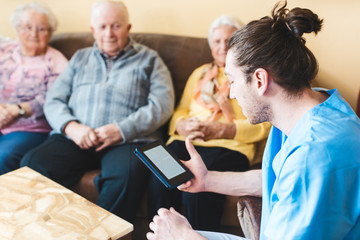 Nurse reading to senior men and women from a story in an e-book