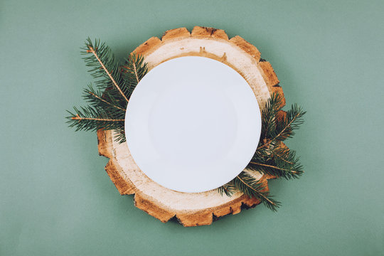 Festive Christmas natural style table setting with white plate on wood cut platters and fir tree branches on green blue background. Flat lay, top view, copy space