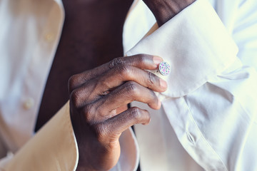 Closeup photo shoot of african american man in white open shirt with diamond cufflink in hand.