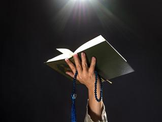 Quran or Kuran ( the islamic holy book) on black