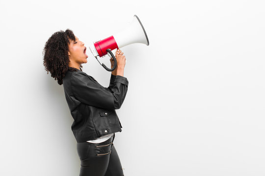 young pretty black woman with a megaphone wearing a leather jacket against white wall