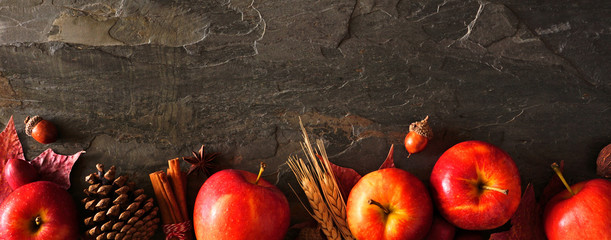 Autumn long border banner of apples, leaves, and fall decor. Top view on a dark stone background with copy space.