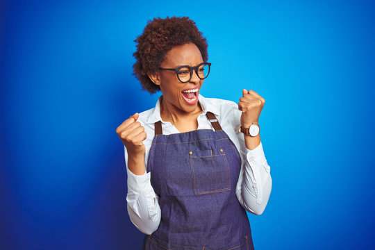 Young african american woman shop owner wearing business apron over blue background very happy and excited doing winner gesture with arms raised, smiling and screaming for success