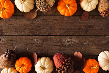 Fall double border of mixed pumpkins and acorn decor. Above view on a rustic dark wood background...