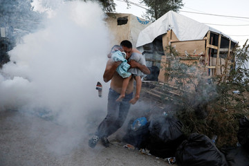 A migrant carries a boy as they flee tear gas fired by riot police during a demonstration, following a fire in Moria camp on the island of Lesbos