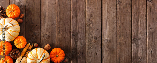 Autumn corner border banner of pumpkins and fall decor on a rustic wood background with copy space