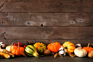 Autumn border arrangement of assorted pumpkins, gourds and fall decor. Side view against a rustic...