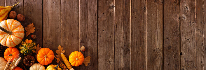 Autumn corner border banner of pumpkins, gourds and fall decor on a rustic wood background with copy space