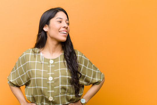 young pretty hispanic woman looking happy, cheerful and confident, smiling proudly and looking to side with both hands on hips against brown wall