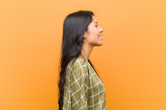 young pretty hispanic woman on profile view looking to copy space ahead, thinking, imagining or daydreaming against brown wall
