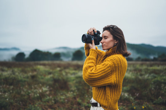 photographer traveler take photo on video camera closeup on background autumn foggy mountain, tourist shooting nature mist landscape outdoor, hobby adventure concept, copy space mockup