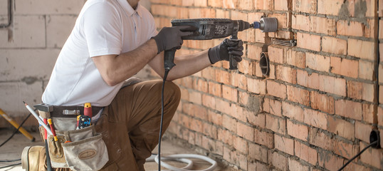 Handyman uses jackhammer, for installation, professional worker on the construction site. The...