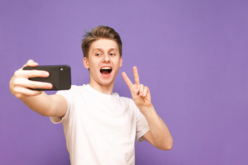 positive boy takes a selfie,wearing a white T-shirt, standing on a purple background and posing on the camera.Happy young man makes selfie. Shows a sign of peace in the camera of a smartphone