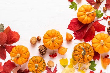Festive autumn pumpkins decor with fall leaves, berries, nuts on white background. Thanksgiving day or halloween holiday, harvest concept. Top view flat lay composition with copy space for greeting