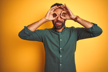 Young indian businessman wearing elegant shirt standing over isolated white background doing ok gesture like binoculars sticking tongue out, eyes looking through fingers. Crazy expression.