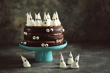 Homemade Chocolate Cake with Chocolate cream and Meringue Ghost and Eyes for Halloween Party.