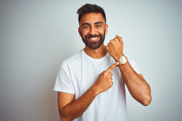 Young indian man wearing t-shirt standing over isolated white background In hurry pointing to watch time, impatience, looking at the camera with relaxed expression