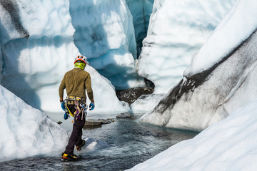 Ice climber walking through a river toward a large ice cave on the Matanuska Glacier in Alaska. Wall mural