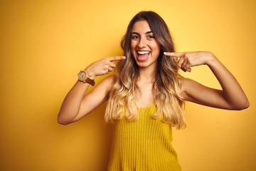 Young beautiful woman wearing t-shirt over yellow isolated background smiling cheerful showing and pointing with fingers teeth and mouth. Dental health concept.