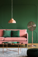 Copper accents in elegant pastel pink and emerald green interior with sofa and coffee table