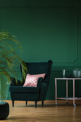 Copy space on empty dark green wall of stylish living room with comfortable armchair and pastel pink coffee table