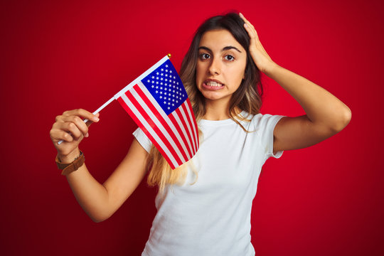 Young woman holding united states of america flag over red isolated background stressed with hand on head, shocked with shame and surprise face, angry and frustrated. Fear and upset for mistake.